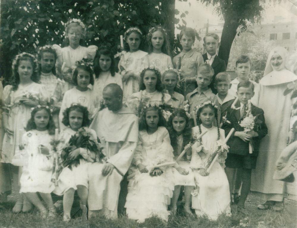 Grupowa fotografia dzieci, które 18 VI 1944 r. przystąpiły do I Komunii Św. w kaplicy Najświętszej Marii Panny Jazłowieckiej przy ul. Kazimierzowskiej na Mokotowie. Pierwsza po prawej stronie zakonnika, w długiej sukience z falbankami i krzyżykiem na szyi siedzi Teresa Winkler (wówczas Herbst) Dar Teresy Winkler.