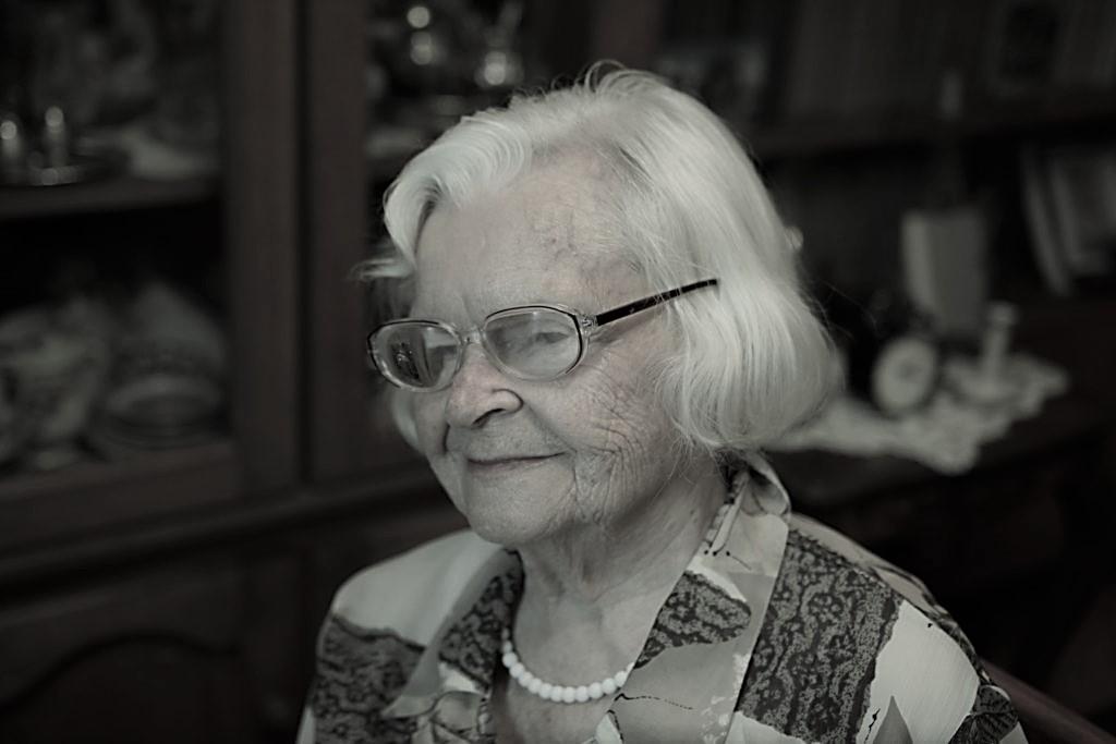 Siedząca Maria Ciesielska, w okularach, uśmiechająca się. W tle wystrój mieszkania.