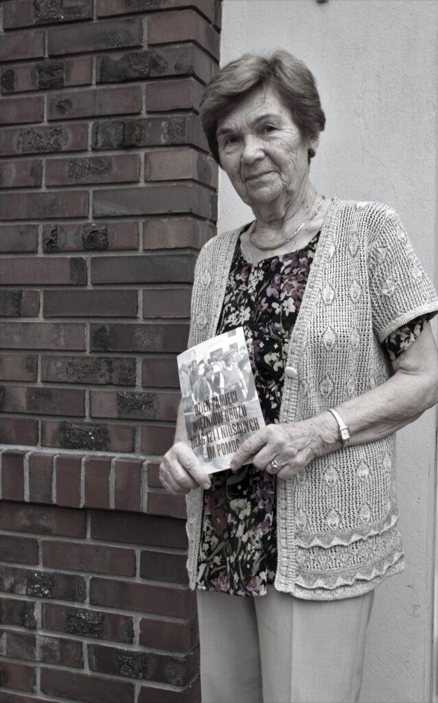 Zdjęcie ze stojącą Janiną Antoszewską, trzymającą w ręku zaproszenie na obchody Dnia Pamięci Więźniów Obozu Dulag 121 i niosących im pomoc. W tle ściana przy wejściu do Muzeum Dulag 121.